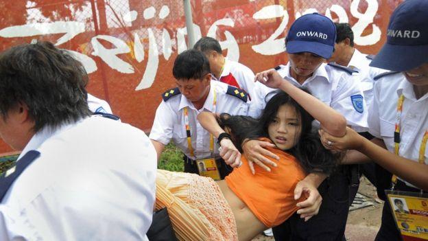 Pekin Olimpiyatları'nda Tibet yanlısı göstericiyi gözaltına alan güvenlik güçleri.