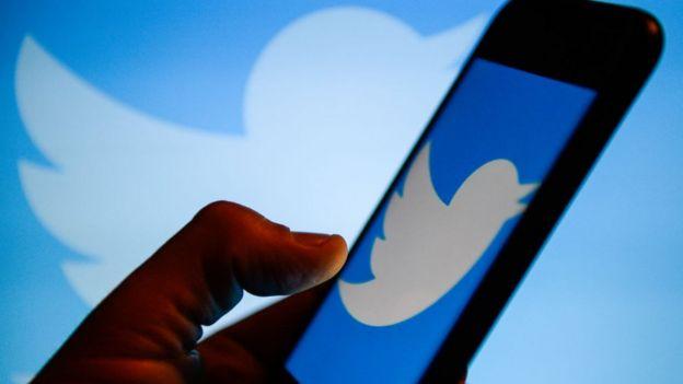 Logo de Twitter en el fondo de la foto y en la pantalla de un celular.