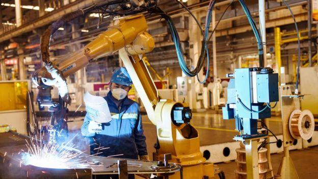 河北一家汽车工厂工人在生产线上带着口罩开工。