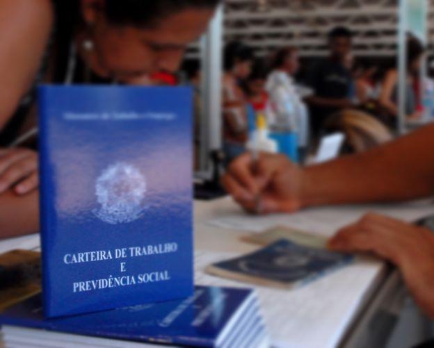 Imagem mostra carteiras de trabalho empilhadas sobre uma mesa em que uma pessoa escreve e uma mulher observa