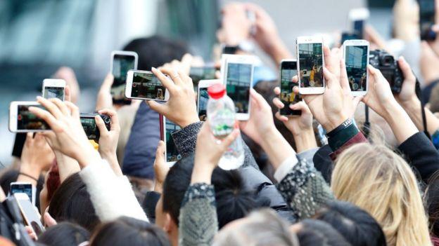 Gente sacando fotos con sus teléfonos