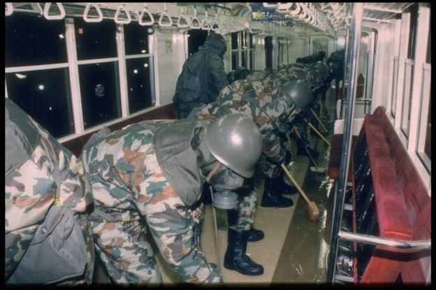 Equipos del Ejército nipón limpiando vagones del metro tras el ataque de 1995.