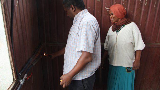 Zenebech Alemayehu watches as a friend lights the gas supply from her digester