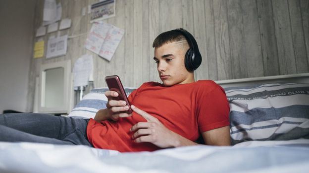 Adolescent looking a his phone while lying on his bed