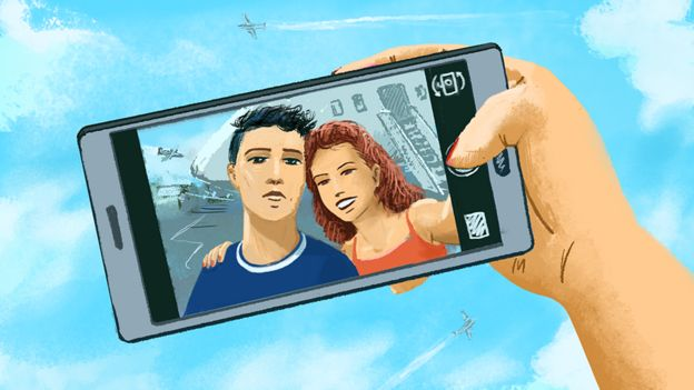 Uma mão segura um telefone celular, mostrando uma imagem de um casal.
