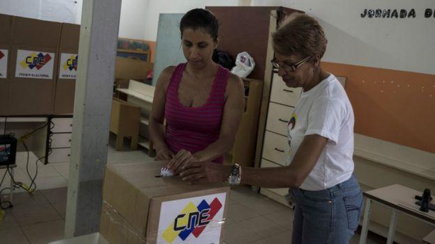 Dos personas votan.