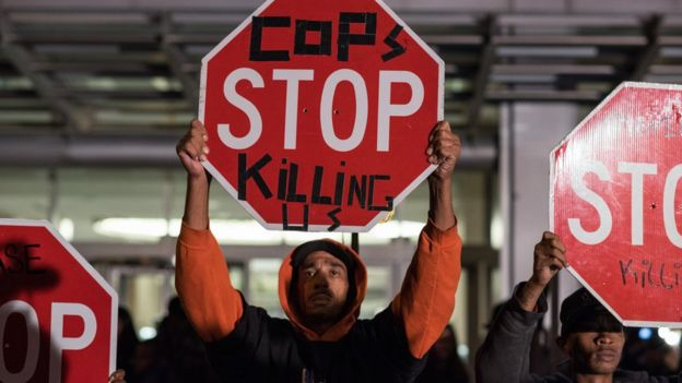 "Protesters hold ""cops stop killing us"" signs"