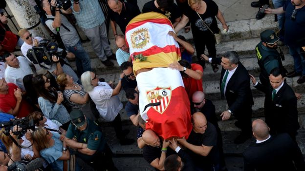 The coffin with the remains of Spanish footballer Jose Antonio Reyes, covered with the flags of the village of Utrera and Sevilla FC football team, is carried on shoulders to the Santa Maria de Mesa church in Utrera during his funeral, 3 June 2019