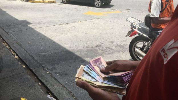 Funcionário de posto de gasolina contando dinheiro