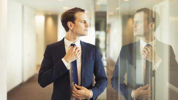 شخص ينظر بغرور إلى نفسه في المرآة