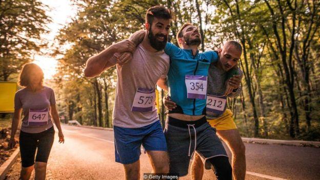 Dois maratonistas carregam um terceiro entre eles, machucado; os três homens são observados por uma outra corredora, mulher