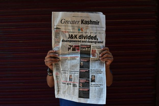 """A Kashmiri boy poses with a newspaper headline """"J&K Divided"""" during curfew in Srinagar, Indian Administered Kashmir on 06 August 2019. Curfew Continues in Kashmir after the Scrapping of Article 370 on 06 August 2019. Curfew has been implemented across Jammu and Kashmir to thwart any protests. All the communication channels have been blocked across the valley. (Photo by Muzamil Mattoo/NurPhoto via Getty Images)"""