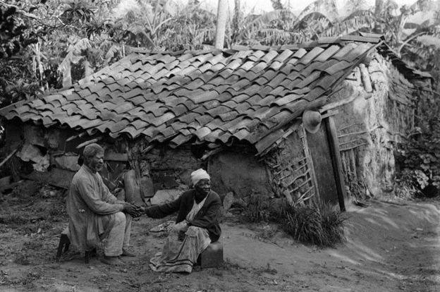 Imagem mostra casal de ex-escravos sentado em frente a barraco, de mãos dadas, em Porto Alegre, no ano de 1900. Crédito: Acervo do Museu de Porto Alegre Joaquim Felizardo/Lunara