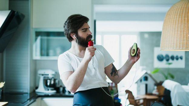 yemek pişirirken şarkı söyleyen sakallı bir adam