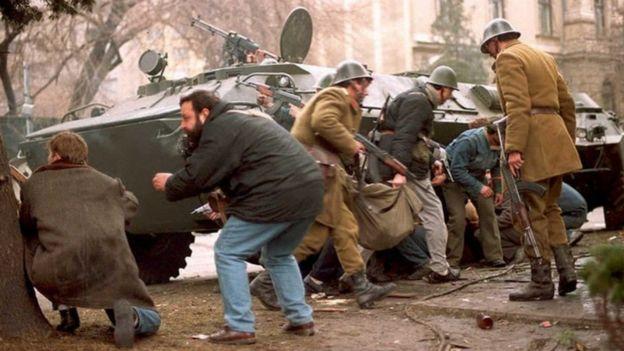 Militares e civis romenos se escondem de atiradores no centro de Bucareste, em 24 de dezembro de 1989
