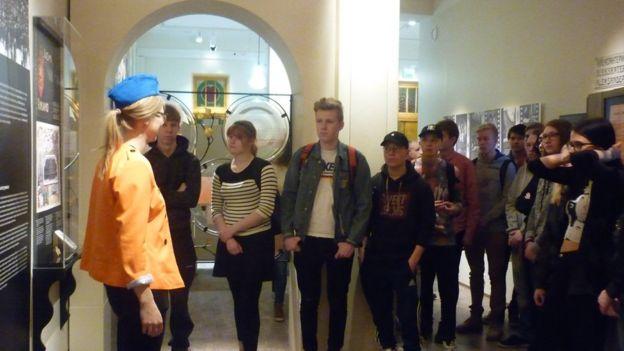 Một nhóm học sinh phổ thông đang nghe thuyết minh tại bảo tàng.
