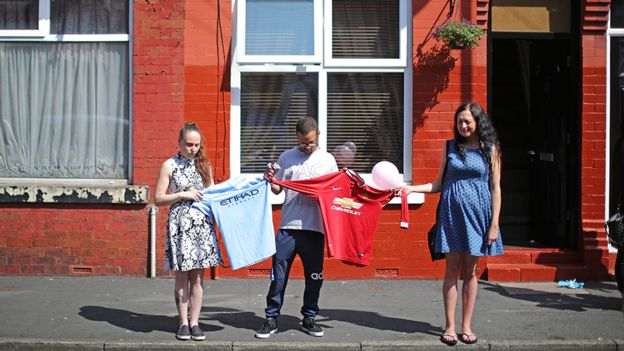 Three people hold up a Manchester United shirt and a Manchester City shirt 98728fd02a78