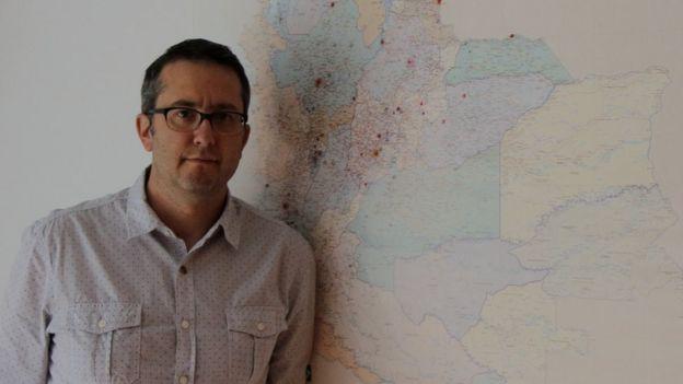 Natalio Cosoy junto al mapa que hay en la oficina de la corresponsalía de BBC Mundo en Colombia.