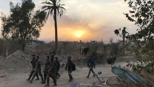 Syrian government forces walk through a road in a north-eastern district of Deir al-Zour