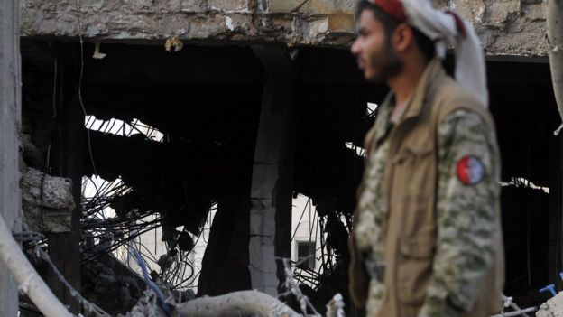 A Yemeni man inspecting air strike damage