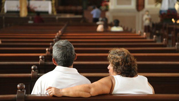 People sit in a pew in a cathedral in El Salvador