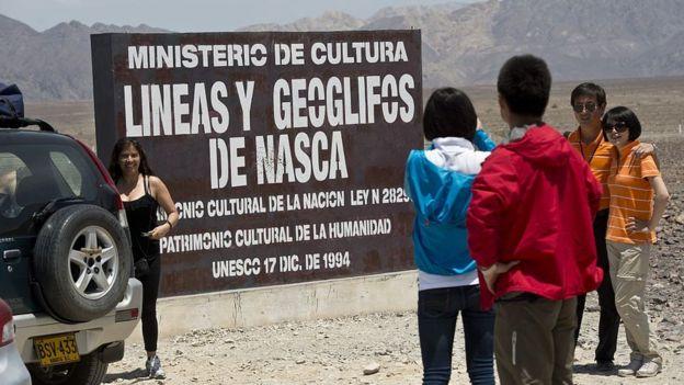 Personas posando ante un cartel de Ministerio de Cultura antes de entrar a ver las líneas de Nasca.