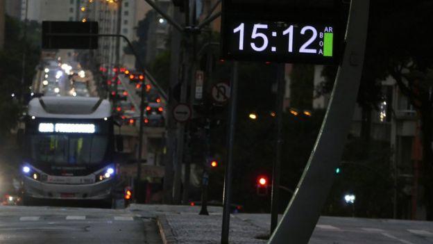 Via de São Paulo repleta de veículos, com relógio de rua marcando 15h12 e luminosidade fraca