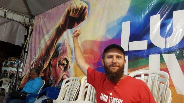 Inácio Sadovski sorri e levanta o braço em frente a cartaz com foto de Lula fazendo o mesmo gesto