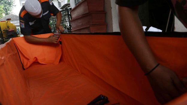 Полицейские в Индонезии делают специальный гроб для жертв коронавируса