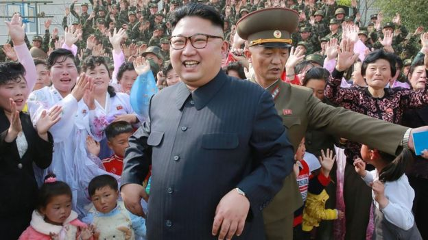 Kim Jong-un on May 5, smiling and standing in front of seemingly joyous citizens