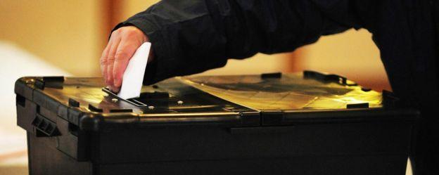 Man placing vote in ballot box