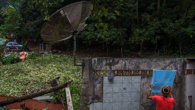 Homem pendura roupa perto do varal ao lado de floresta