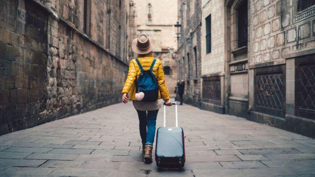 Mujer caminando con una maleta por una ciudad
