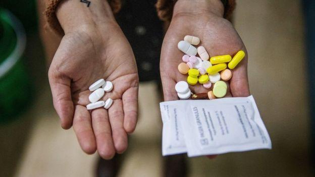 Dos manos con pastillas. A la izquierda solo unas cuantas, a la derecha muchas más.