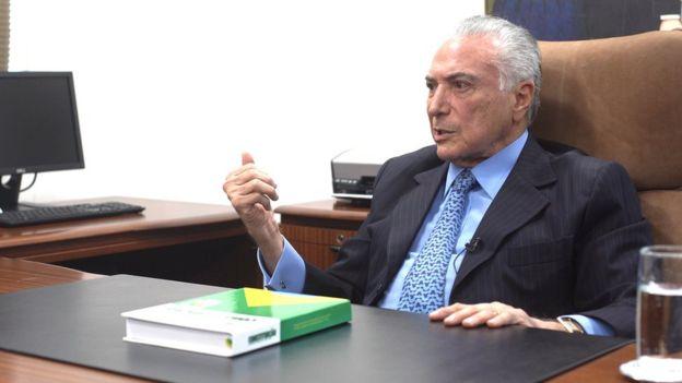 Temer dá entrevista sentado em poltrona e diante de mesa no seu escritório, sobre a qual está um exemplar da Constituição
