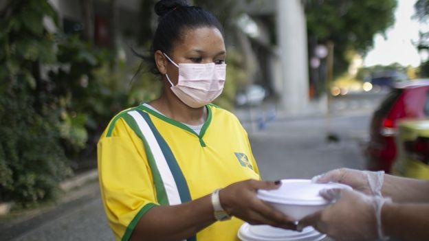 Mulher com máscara recebe alimentos de projeto de caridade