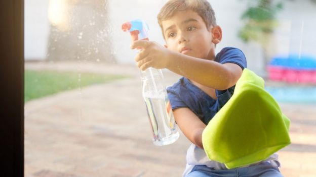 A young boy cleaning a window using a chemical spray and a cloth.