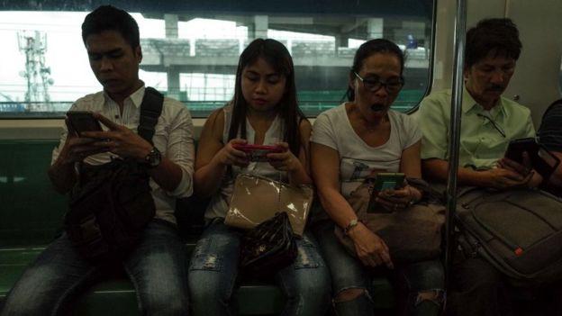 Filipinos pegados a sus celulares en un tren en Manila