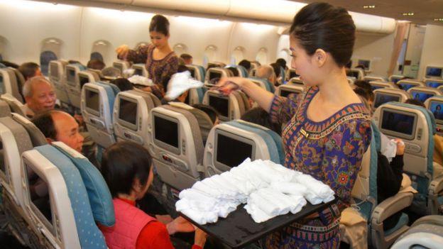 Funcionárias da Singapore Airlines distribuem toalhas para passageiros
