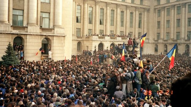 Protesters in Bucharest wave Romanian flags as they stage an anti-communist demonstration at Republic Square, 21 December 1989