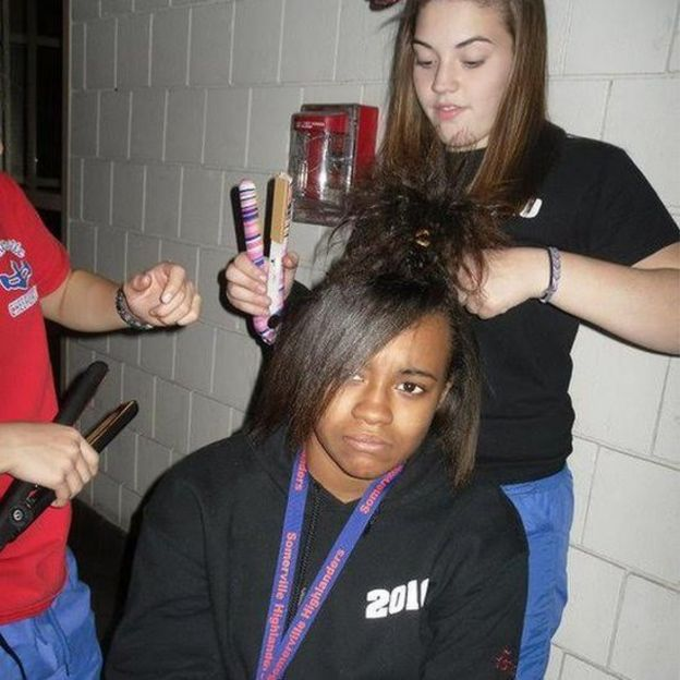 Tameka Amado gets hair straightened by teammates for cheerleading squad