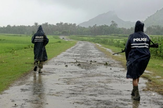 Myanmar police officers patrol a road in northern Rakhine, 26 August