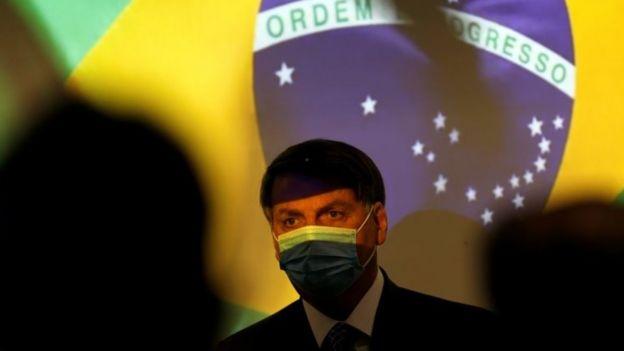 Jair Bolsonaro com a bandeira do Brasil ao fundo