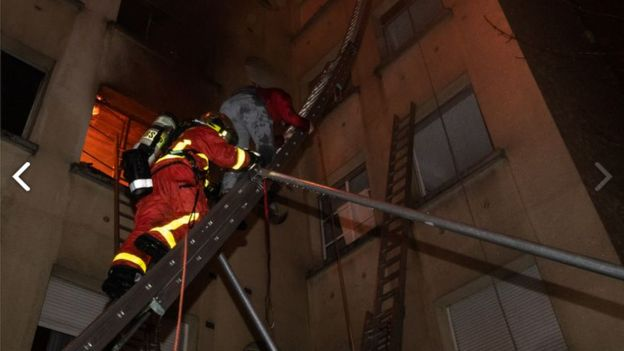 Firefighter helping a woman escape the building using a ladder