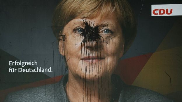 Large poster of Angela Merkel has been covered in black splash of paint over her face