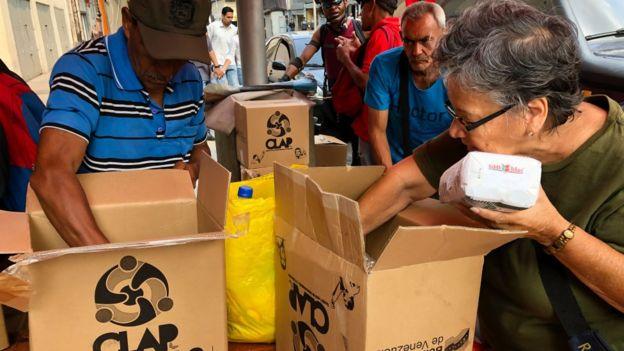 Venezolanos abriendo unas cajas CLAP