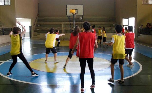 孩子们玩Korfball,他们中的一些人将手放在空中,因为一个球在靠近黄色球门的高空飞翔,高空