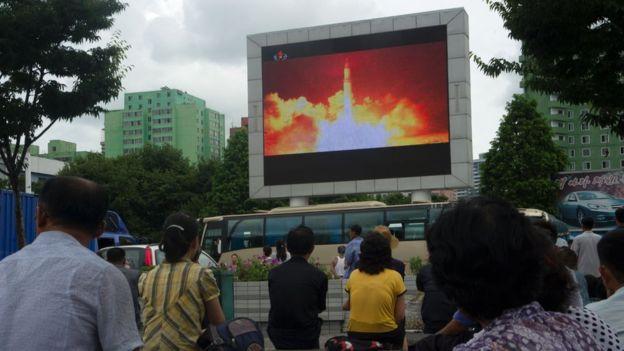 Norcoreanos viendo en una plaza de Pyongyang el lanzamiento de un misil.