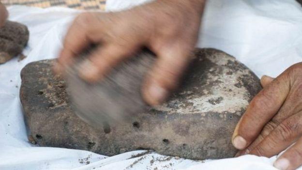 Hombre moliendo granos sobre una piedra