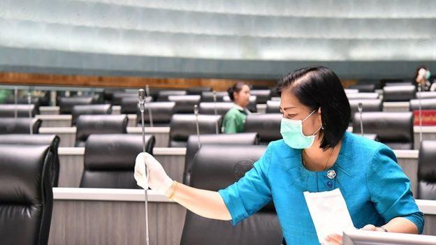 Una mujer limpia un micrófono en el Parlamento de Tailandia.